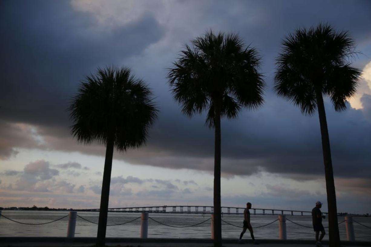 """In this June 4, 2019, photo two people walk along the water in the early morning sunrise near downtown Miami in Key Biscayne, Fla. Some debts that bring the promise of opportunity, like student loans or mortgages, might seem """"good,"""" but that's not always the case. And having credit card debt isn't always bad. What makes debt """"good"""" or """"bad"""" depends on how it fits into your overall financial picture."""