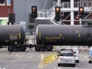 FILE - In this Feb. 13, 2018, file photo, automobile traffic waits at a train crossing as train cars that carry oil are pulled through downtown Seattle. Attorneys general for North Dakota and Montana have petitioned the Trump administration Wednesday, July 17, 2019, to overrule a Washington state law that imposes safety restrictions on oil shipped by rail from the Northern Plains.