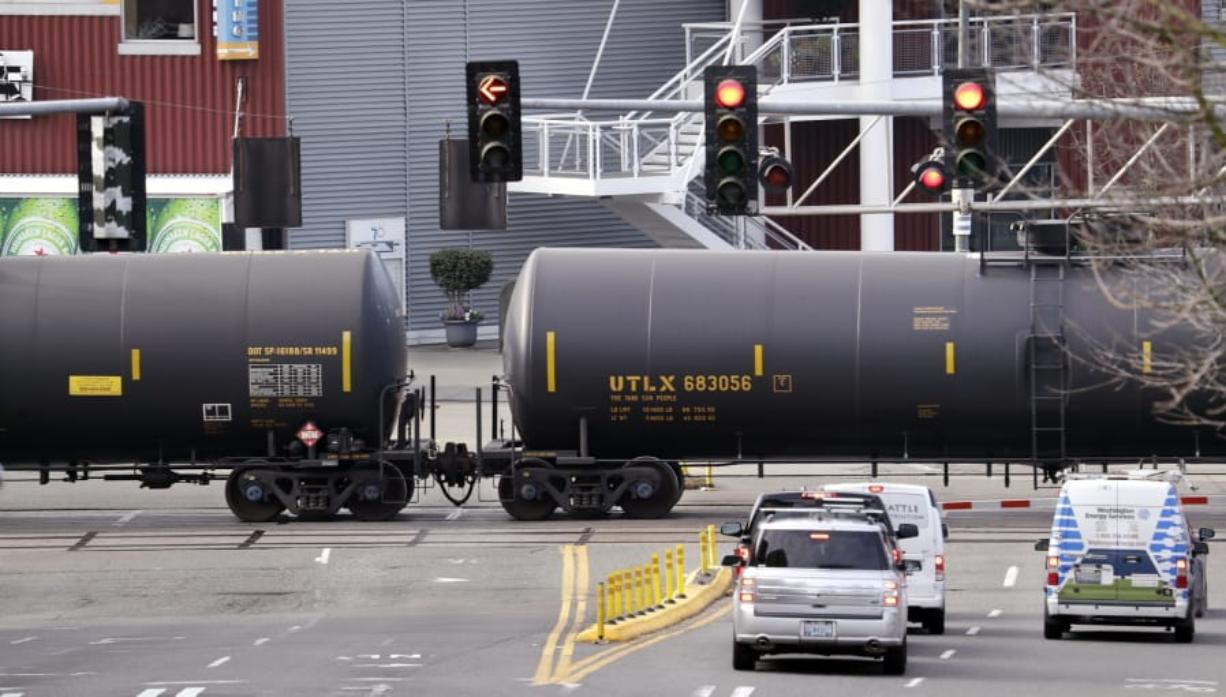 Automobile traffic waits in February 2018 at a train crossing as train cars that carry oil are pulled through downtown Seattle.
