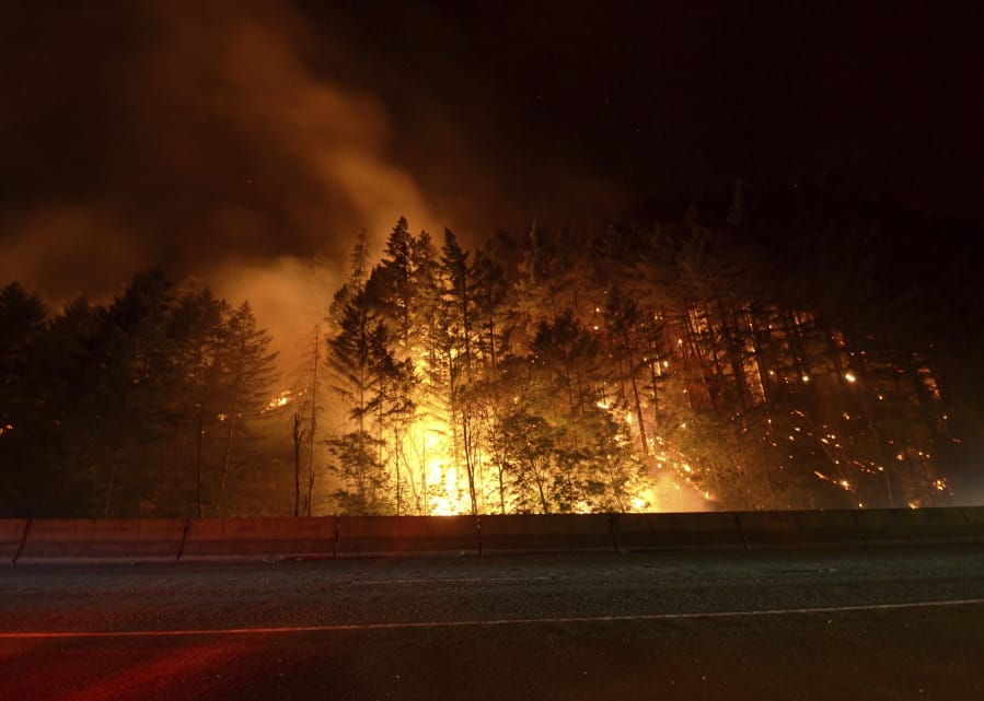 In this Saturday, July 27, 2019 photo, flames rage next to Interstate 5 south of Canyonville, Ore., during the Milepost 97 Fire. Interstate 5 drivers should expect delays Tuesday, July 30, 2019, in both directions as fire crews remove hazardous trees south of Canyonville in southwestern Oregon. The Oregon Department of Transportation says traffic will be slowed in both directions between mileposts 88 and 101 from 7 a.m. to 10 a.m. Oregon's Milepost 97 fire is believed to have started Wednesday because of an illegal campfire.