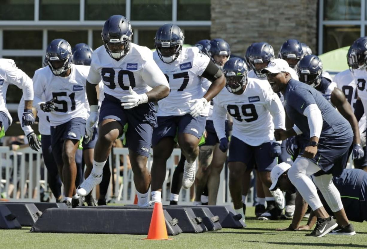 Seahawks defensive tackle Jarran Reed (90) runs a drill with teammates Thursday. Reed learned this week he will be suspended from the first six games of the season by the league. Ted S.