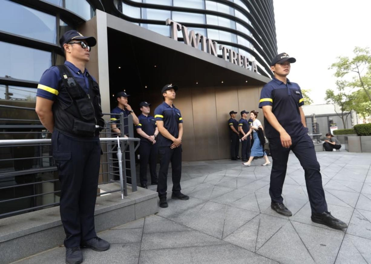 South Korean police officers stand guard against possible rallies against Japan in front of a building where the Japanese embassy is located in Seoul, South Korea, Friday, July 19, 2019. South Korean police say a man has set himself on fire in front of the Japanese Embassy in Seoul amid rising trade disputes between Seoul and Tokyo.