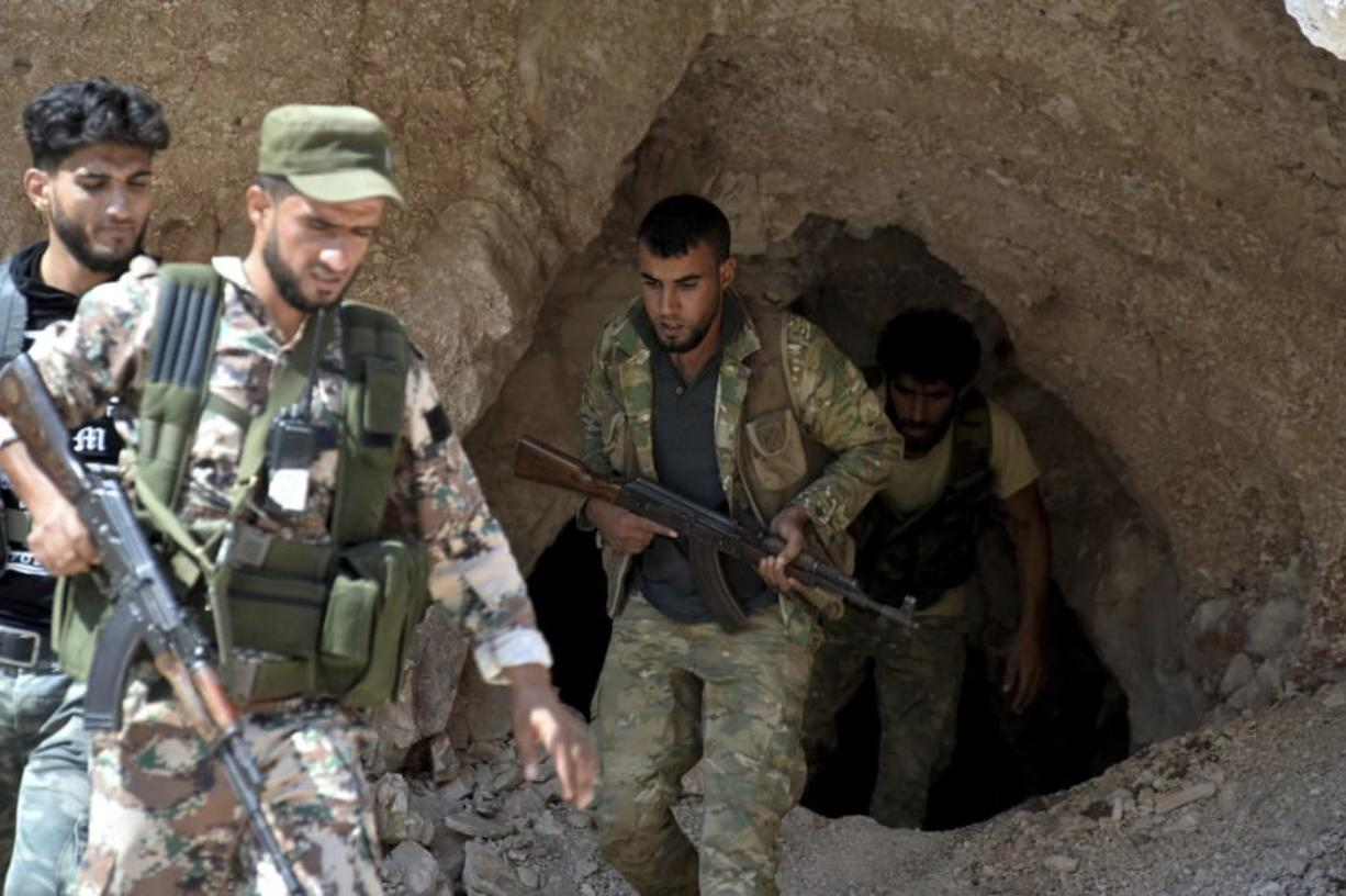 FILE - In this Sept. 9, 2018 file photo, fighters with the Free Syrian army exit a cave where they live, on the outskirts of the northern town of Jisr al-Shughur, west of Idlib, Syria. n two months of intensive airstrikes and bombardments on the rebel-controlled province of Idlib, Syrian government forces and their Russian allies have failed to make progress against battle-hardened insurgents. (Ugur Can/DHA via AP, File)