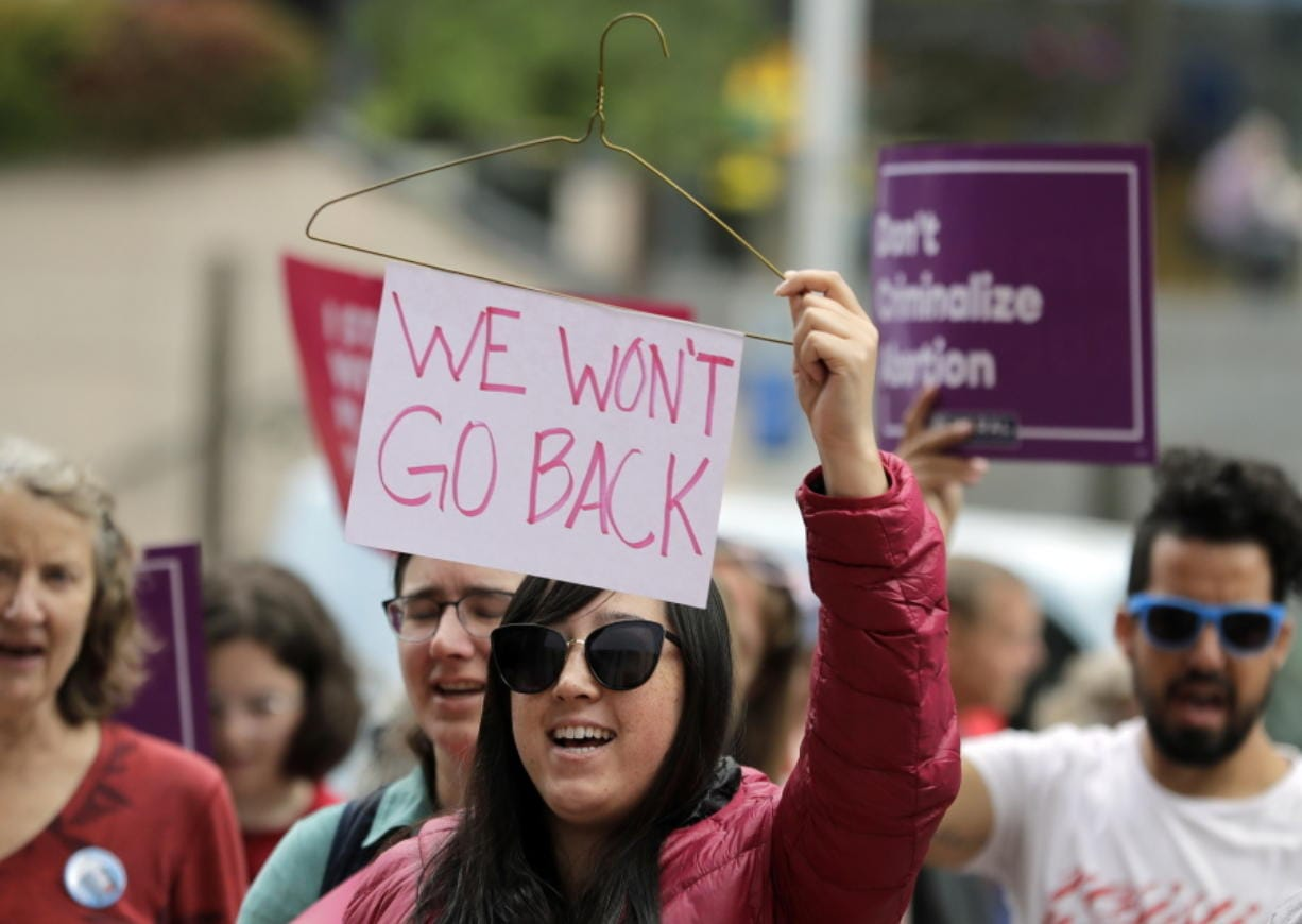 "Hillary Namba, of Seattle, holds a wire coat hanger and a sign that reads ""We Won't Go Back"" during a protest on July 10, 2018, in Seattle. Trump administration rules imposing additional hurdles for low-income women seeking abortions are on hold once again. Ted S."