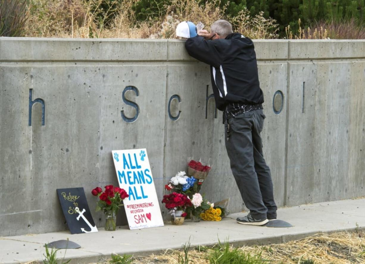 Freeman High School assistant football coach Tim Smetana grieves Sept. 14, 2017, after he placed roses at a memorial following a shooting at the school in Rockford, south of Spokane. Associated Press files