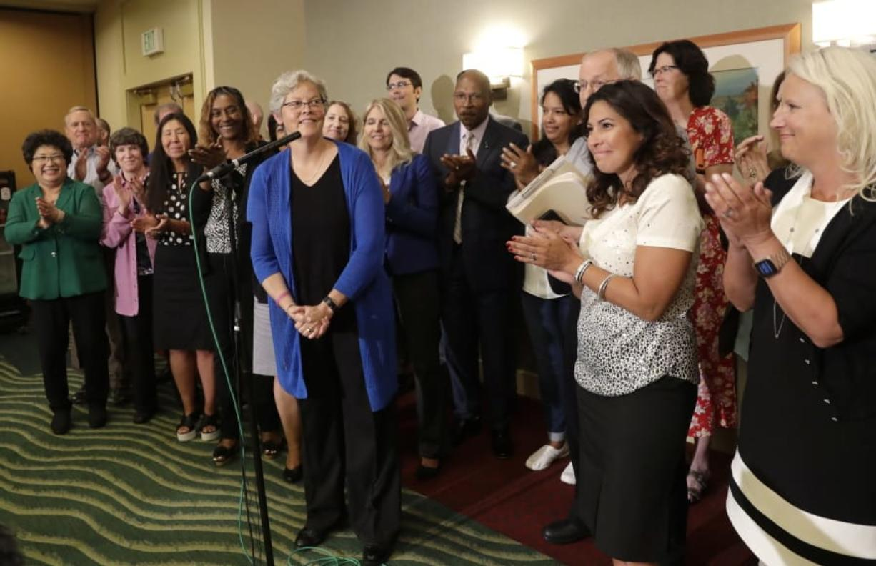 State Rep. Monica Stonier, D-Vancouver, second from right, applauds after Rep. Laurie Jinkins, in blue, was introduced at a news conference following a vote by Democrats choosing Jinkins as speaker of the House. Stonier was one of four female representatives seeking the top spot.