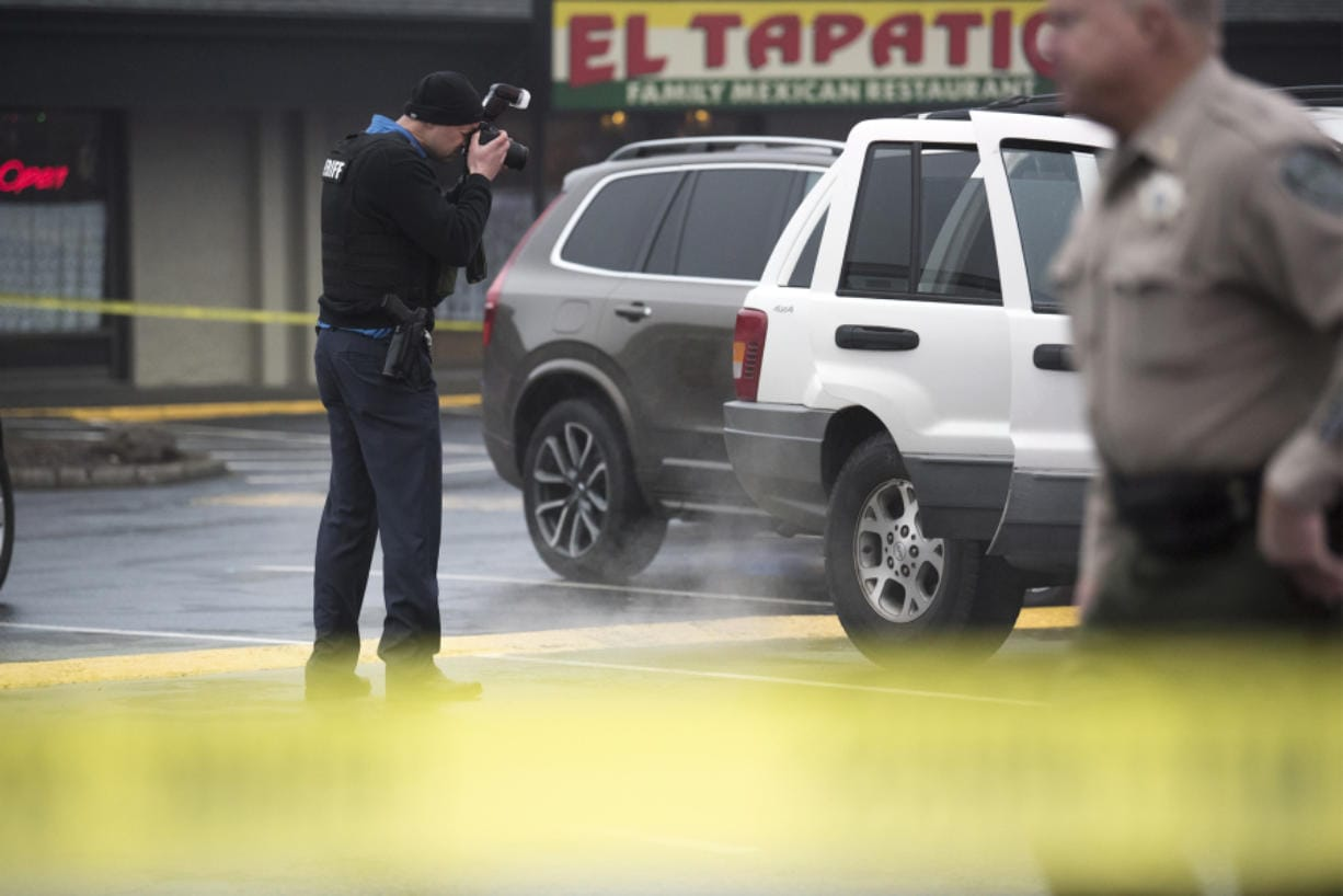 A Clark County Sheriff's investigator photographs the car of a shooting victim at Pacific 63 Center in Hazel Dell on Dec. 10, 2018.