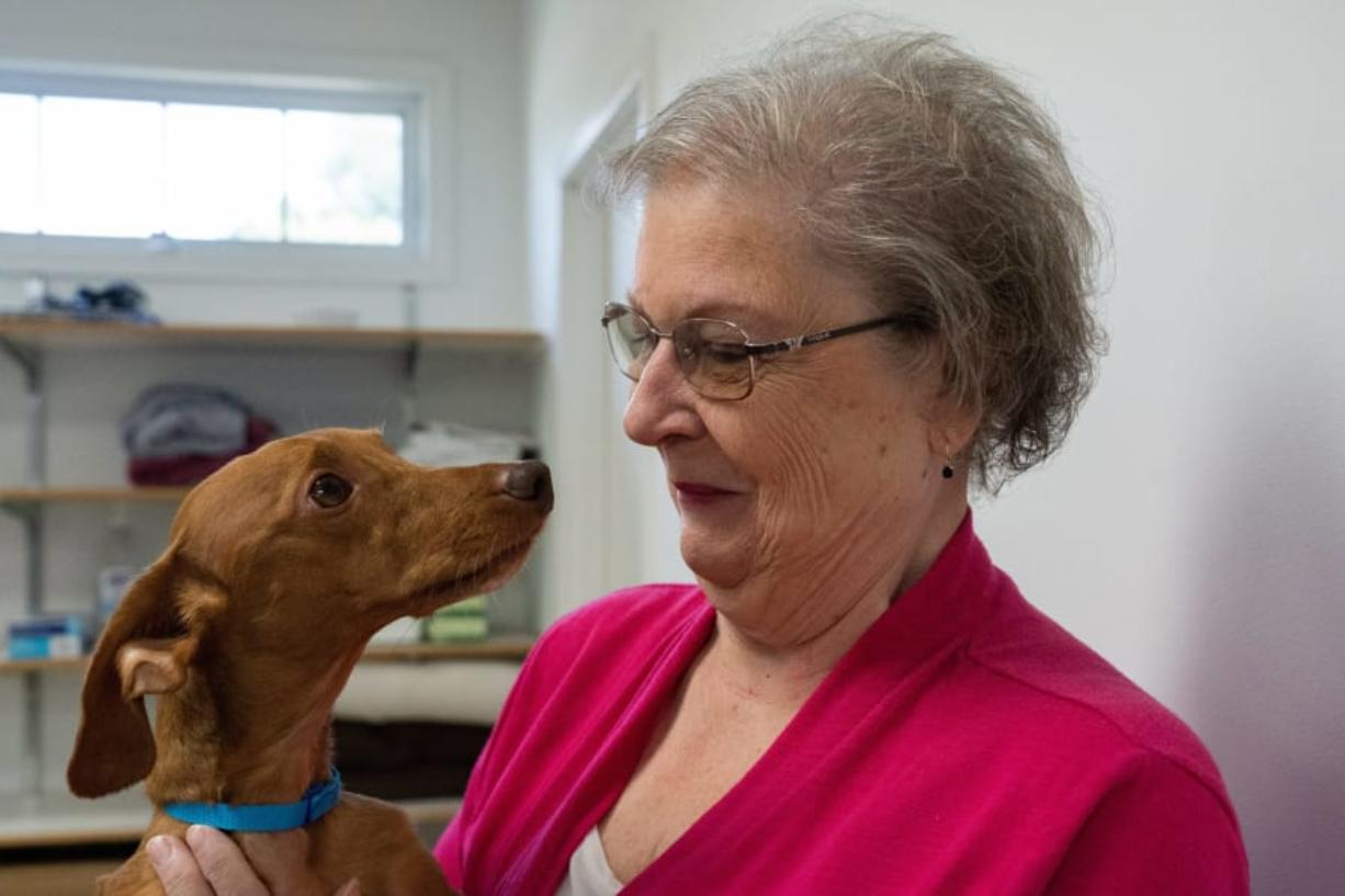 Lorraine Young hugs her dog, Andy, on a visit Aug. 12 to the vet after the dog received emergency spine surgery in July and is now almost fully recovered at St. Francis Veterinary Center in Swedesboro, N.J.