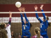 Prairie's Maddi Cederholm (9) spikes the ball as Kelso's Sydney Hall (5) and Isabella Hadaller (11) jump to block during Tuesday night's game at Prairie High School in Camas on Sept. 25, 2018. Prairie won in three sets, 25-10, 25-13, 25-13.