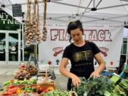Kelly Peters of Flat Tack Farm works at her Vancouver Farmers Market booth.