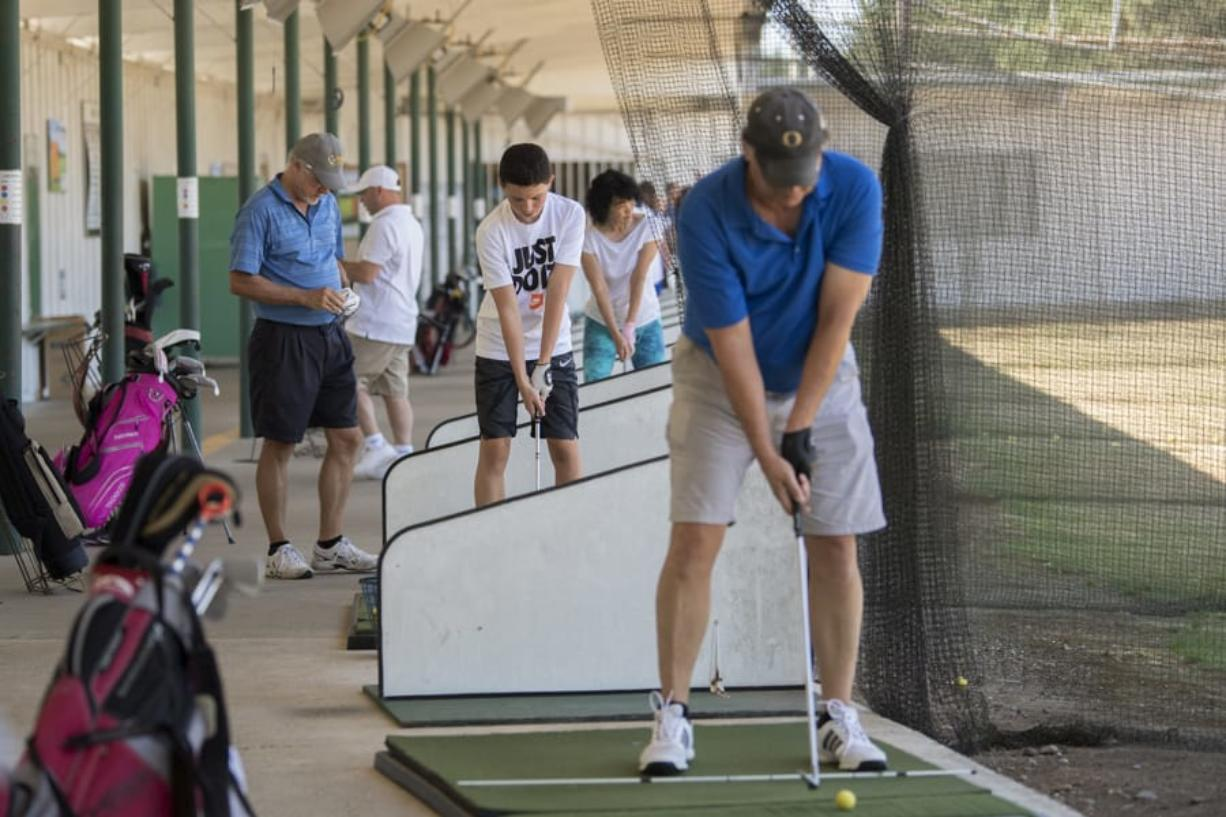 A crowd of golfers including Ridgefield resident Zac Warren, 15, center in white T-shirt, work on their swing during a busy summer afternoon at Vanco Golf Range.