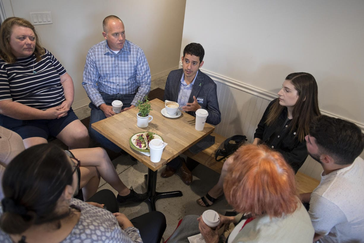 Adam Aguilera, center in gray jacket, chats with voters at River Maiden on Tuesday morning. Aguilera's one of seven seeking the Position 6 seat on the Vancouver City Council.