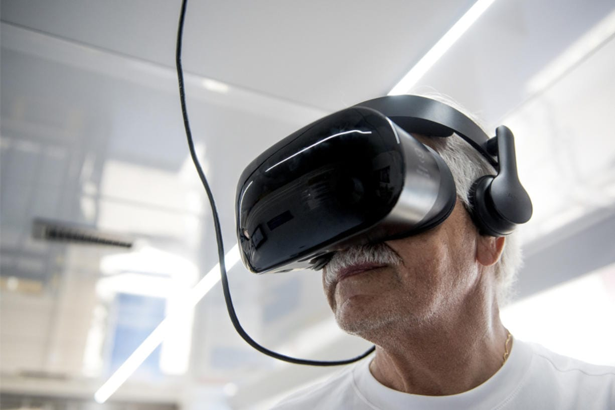 Faiz Humadi, 72, a retired civil engineer originally from Iraq, uses the virtual reality goggles inside the All of Us van in the parking lot of the Grocery Outlet Bargain Market on Fourth Plain Boulevard. The VR goggles teach people about the impact of certain medical breakthroughs.