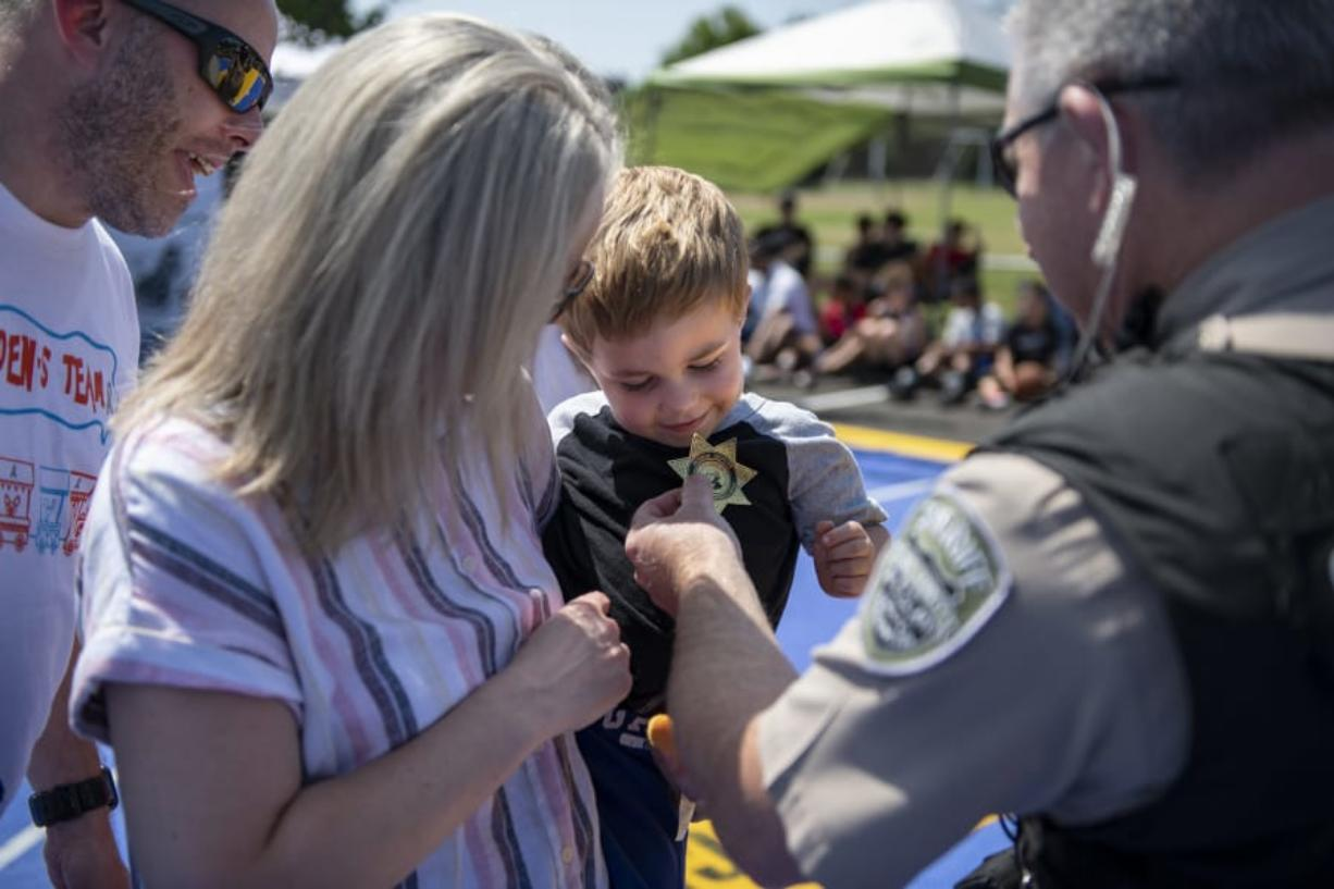 """Jeff Linton, from left, and his wife, Erin, watch as their 4-year-old son Camden is named an honorary deputy by Deputy Darrell Benton of the Clark County Sheriff's Office as part of a Kindness 911 """"sting"""" operation at Skyview High School on Saturday."""