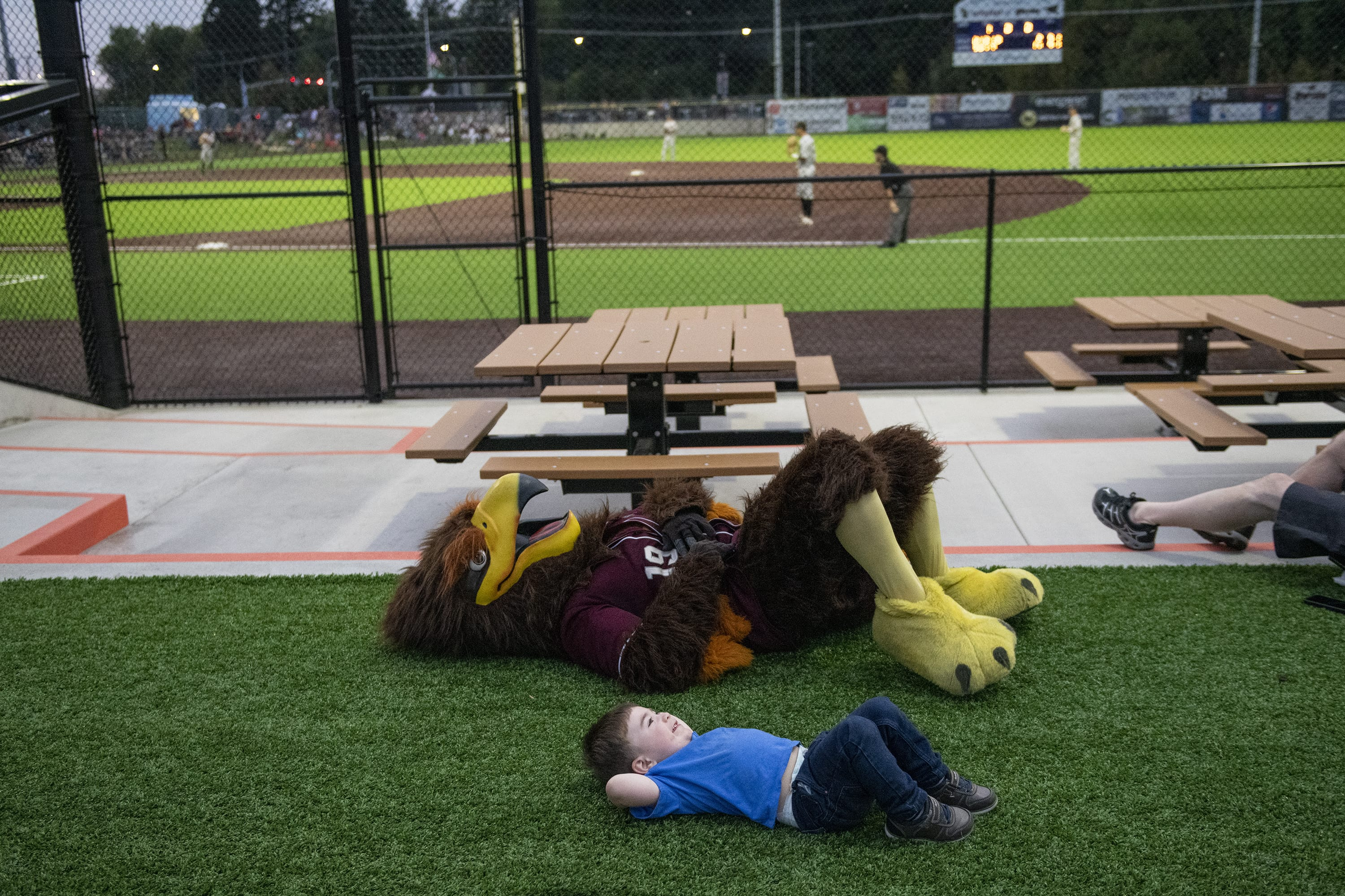 Rally, top, and Colin Jackson, 2, bottom, rest on the ground during the Raptors vs. Elks game at the Ridgefield Outdoor Recreation Complex on Friday evening, August 9, 2019. (Zach Wilkinson/The Columbian)