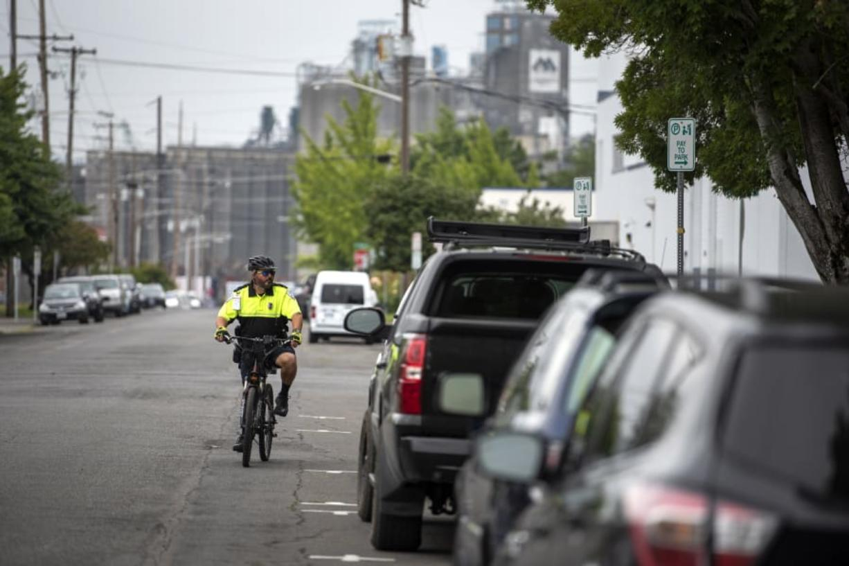 "Vancouver Parking Enforcement Officer Tim Brown patrols the streets surrounding the Clark County Courthouse last week. The area around the courthouse gets busy and the officers' goal, he said, is to create turnover. ""We're not trying to punish people,"" he said."