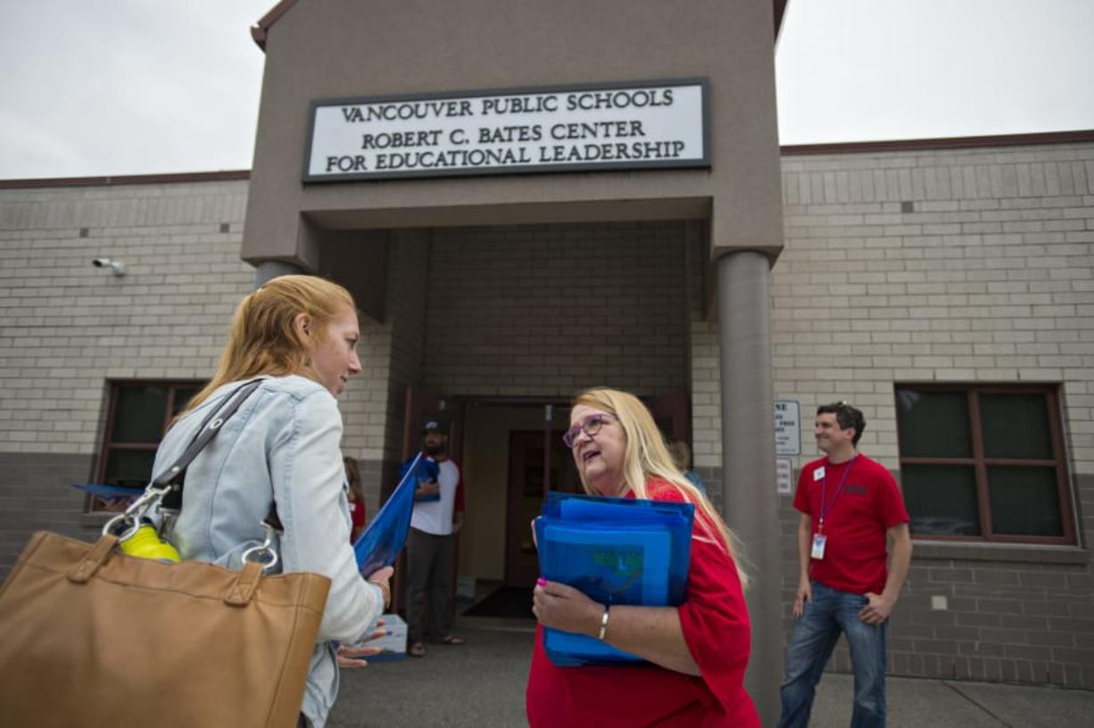 Katie North, a learning support educator at Skyview High School, left, chats with Mona Rominger of the Vancouver Education Association executive board as she attends an educational union meeting at the Bates Center for Educational Leadership on Aug. 9. At top, a colorful button is seen on the T-shirt of Vancouver Education Association executive board member Mona Rominger.