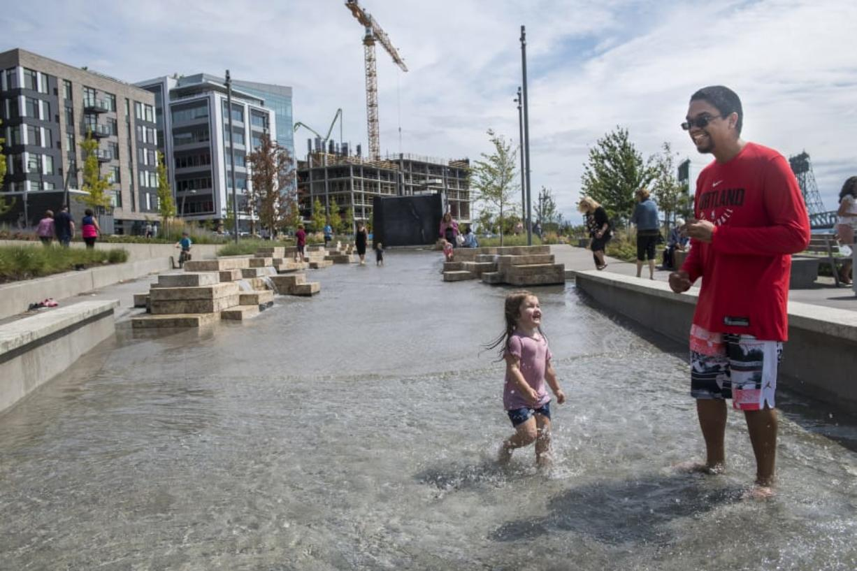 Adaline Sokol, 2, left, and Gage Marshall splash in the new Columbia River water feature Friday afternoon at the Waterfront Vancouver development. The piece opened to the public Friday morning, just in time for passersby to cool their feet in the late-summer heat.