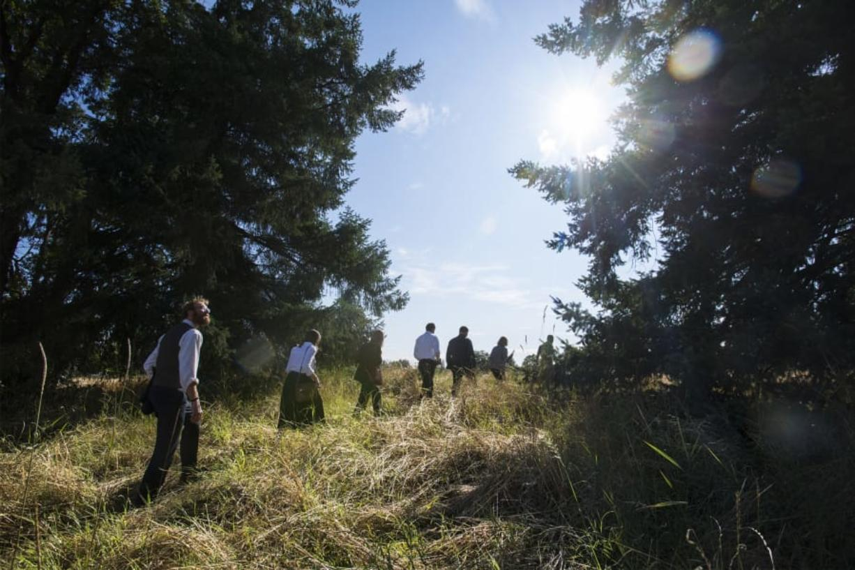 Jonathan Young, interim Vancouver city attorney, left, examines the treeline at the Fenton property on Monday evening during a Vancouver City Council mobile workshop.