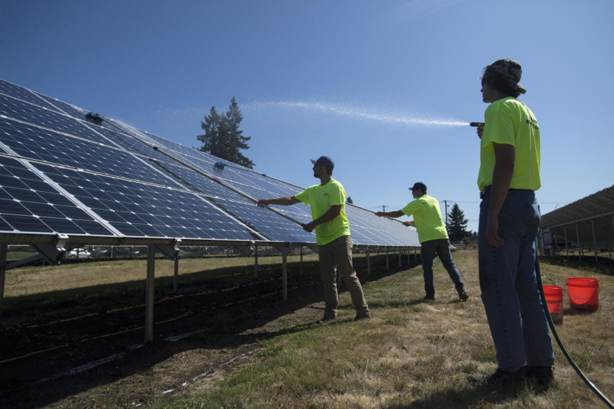 Rafer Stromme, from left, Nick Neathamer and Spencer Black, members of the student grounds crew, clean solar panels Tuesday morning at Clark Public Utilities' operations center in Vancouver. In 2015, Clark Public Utilities launched a program that prompted about 700 customers to invest in the county's largest solar array. The solar panels need to be cleaned to remove dust to maximize energy production, especially in the summer months. Amanda Cowan/The Columbian