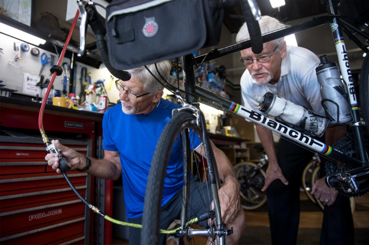 Brothers Mark Roskam, left, and Mike Roskam perform maintenance on Mark's bike at Wheel Deals Bicycles on Monday. The two plan to ride Route 66 starting next month for a fundraiser. Nathan Howard/The Columbian