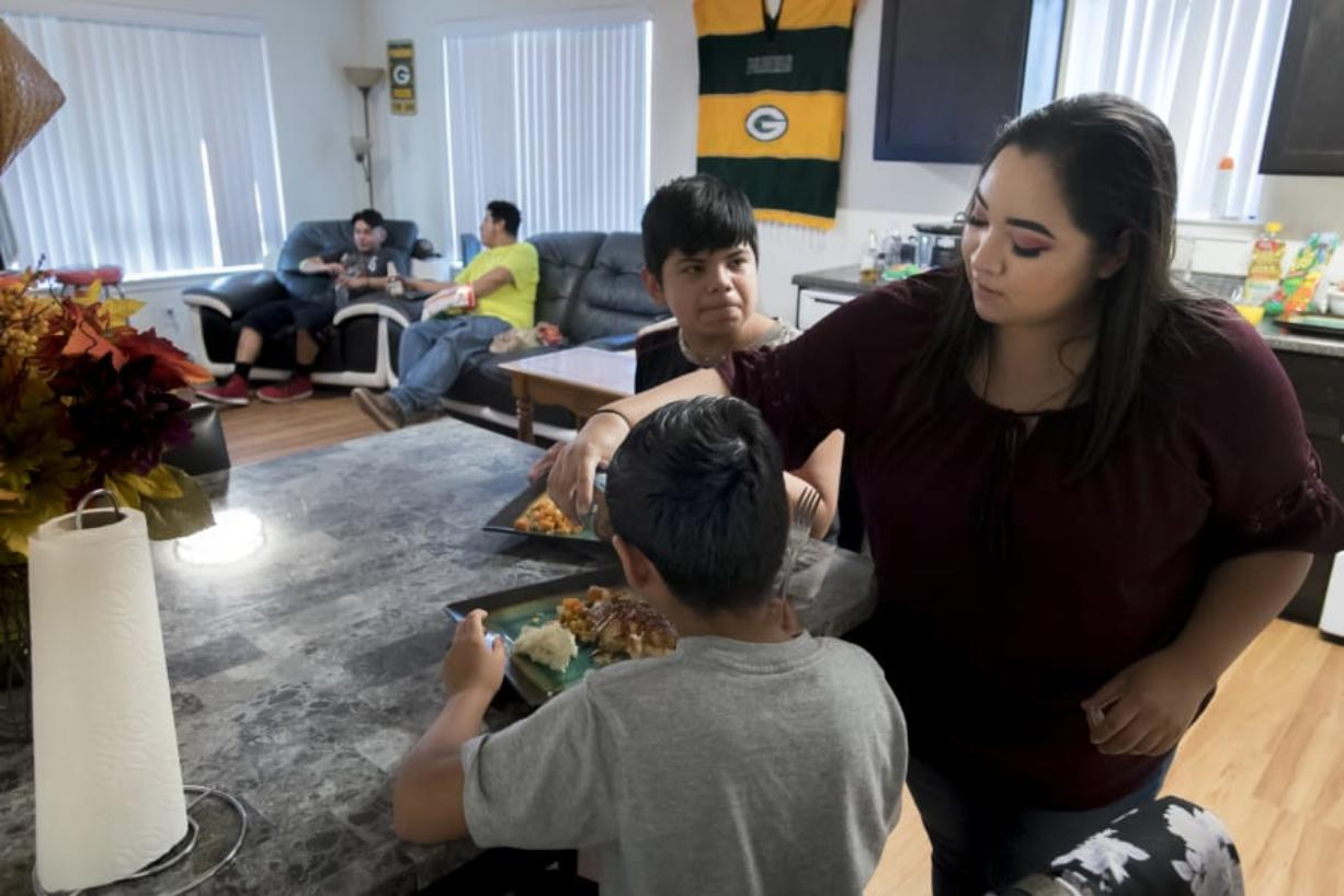 Giovanni Valtierra, 14, left, waits for Vanessa Contreras to finish pouring teriyaki sauce before eating dinner with the rest of his family at their Vancouver apartment on Tuesday evening.