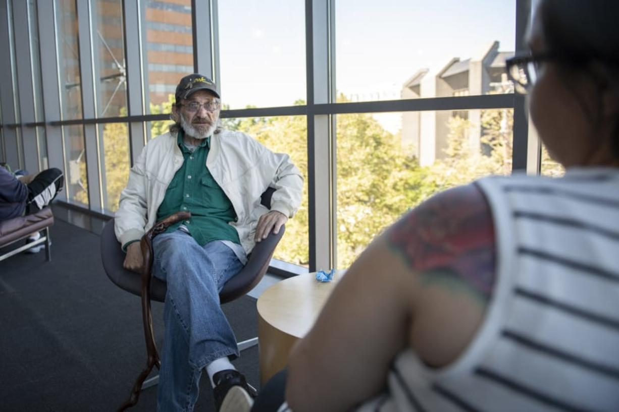 Jack Crowley of Battle Ground speaks with Community Services Northwest case manager Jamie Spinelli at the Vancouver Community Library. Spinelli recently helped Crowley find an apartment after he had been homeless for many years. (Zach Wilkinson/The Columbian)