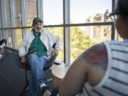 Jack Crowley of Battle Ground speaks with Community Services Northwest case manager Jamie Spinelli at the Vancouver Community Library. Spinelli recently helped Crowley find an apartment after he had been homeless for many years.