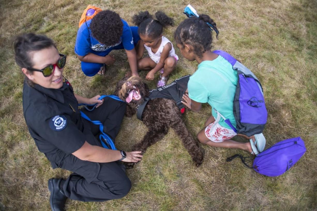 Handler Kanessa Thompson and Apollo greet Eli Fowler, 7, Kyleesia Fowler, 3, and Kara Fowler, 9, at the Washougal Community Fun Day at Hamllik Park. Photos by Nathan Howard/The Columbian