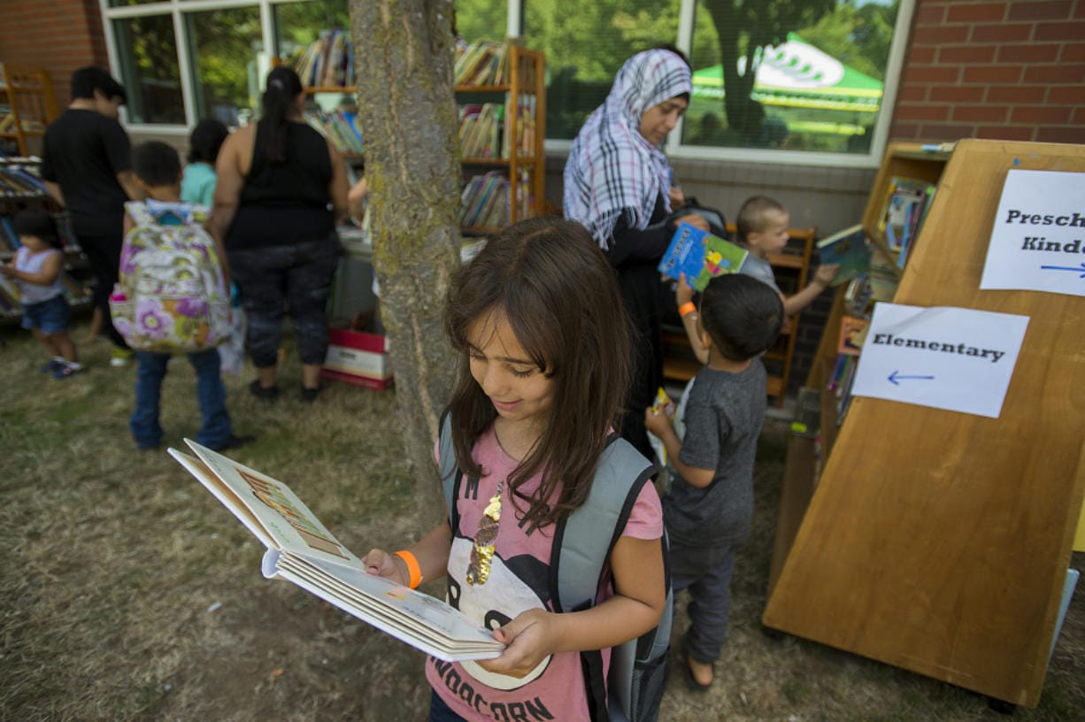 """Vancouver resident Shahed Alhariri, 8, dives into a good story Wednesday afternoon while visiting the free book nook with her family during the annual """"Go Ready!"""" back-to-school event at Hudson's Bay High School. The annual event, now in its fifth year, attracts thousands of families with free resources including haircuts, clothes and immunizations."""