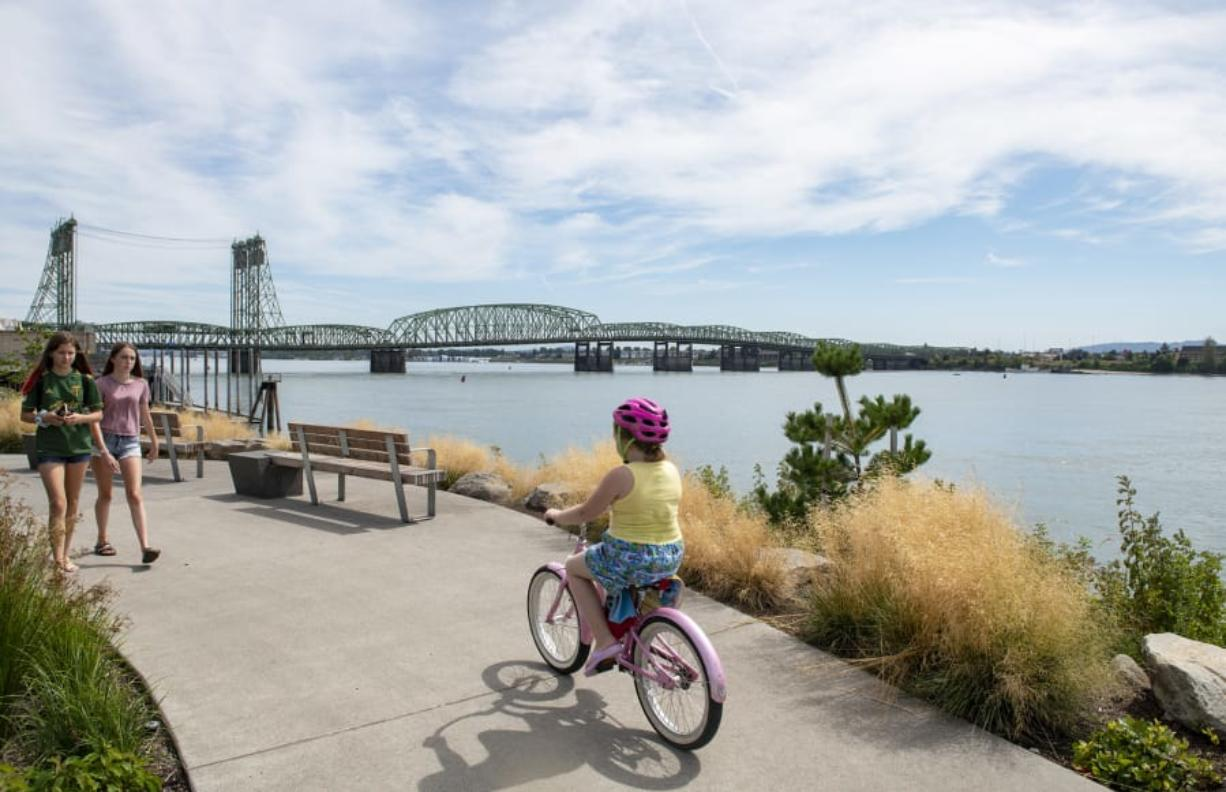 Jaidyn Geesey, left, and Ava Soucy stroll along the Columbia River at Vancouver Waterfront Park on Wednesday afternoon. The Interstate 5 Bridge, which both states want to replace, spans the Columbia River behind them.