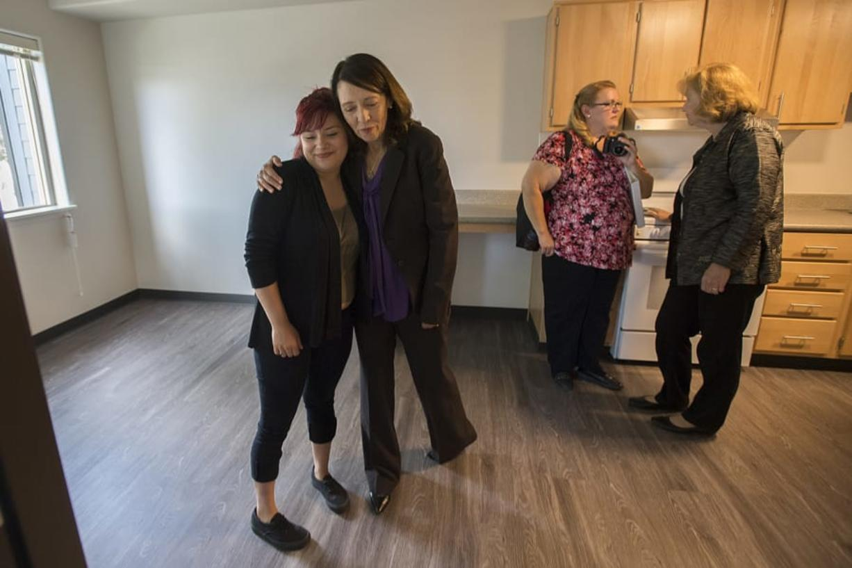 Christina LaCelle, a future Caples Terrace resident, from left, gets a hug from U.S. Sen. Maria Cantwell as they tour the new 28-unit apartment building with Dena Horton, Cantwell's Southwest Washington outreach director, and Vancouver Mayor Anne McEnerny-Ogle on Monday morning. LaCelle said she was looking forward to enjoying her future home with her baby daughter. (Amanda Cowan/The Columbian)
