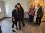Christina LaCelle, a future Caples Terrace resident, from left, gets a hug from U.S. Sen. Maria Cantwell as they tour the new 28-unit apartment building with Dena Horton, Cantwell's Southwest Washington outreach director, and Vancouver Mayor Anne McEnerny-Ogle on Monday morning. LaCelle said she was looking forward to enjoying her future home with her baby daughter.