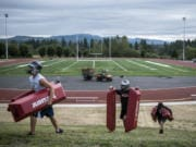 Union players carry drill obstacles from the Union High football field during the first fall practice of the year on Wednesday, Aug. 22, 2019.