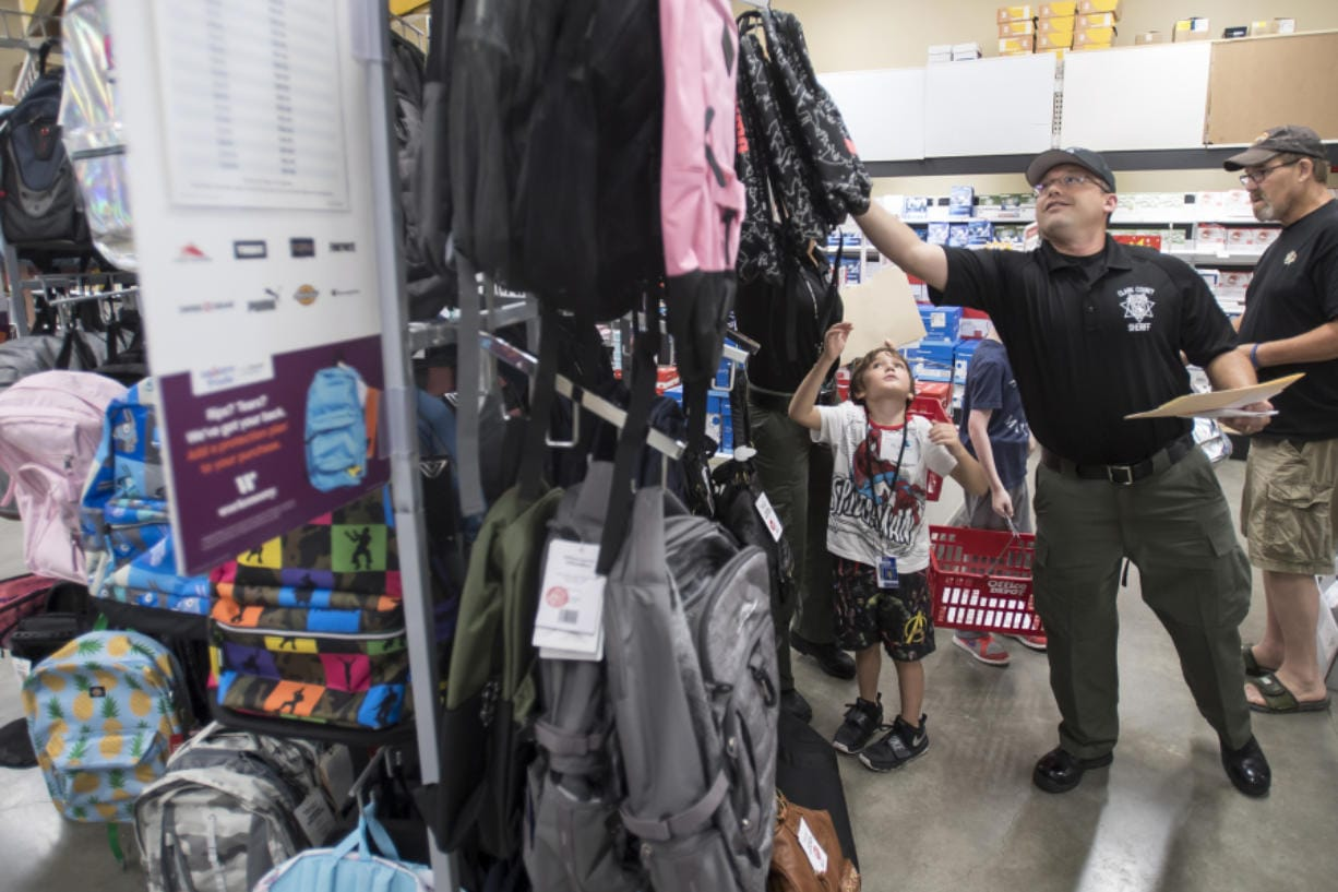 Mitchell Middleton, 6, waits for Clark County sheriff's Deputy Brad Robinson to grab a backpack from the top rack during Tuesday morning's Shop with a Cop event at Office Depot in Hazel Dell.