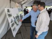 Rob Gartner, vice president of business development for Vesta Hospitality, left, describes the future AC Hotel layout to David Partridge of Vancouver during the ceremonial groundbreaking on Thursday afternoon. At top, a concept art rendering shows the future AC Hotel by Marriott, which broke ground today at Terminal 1.