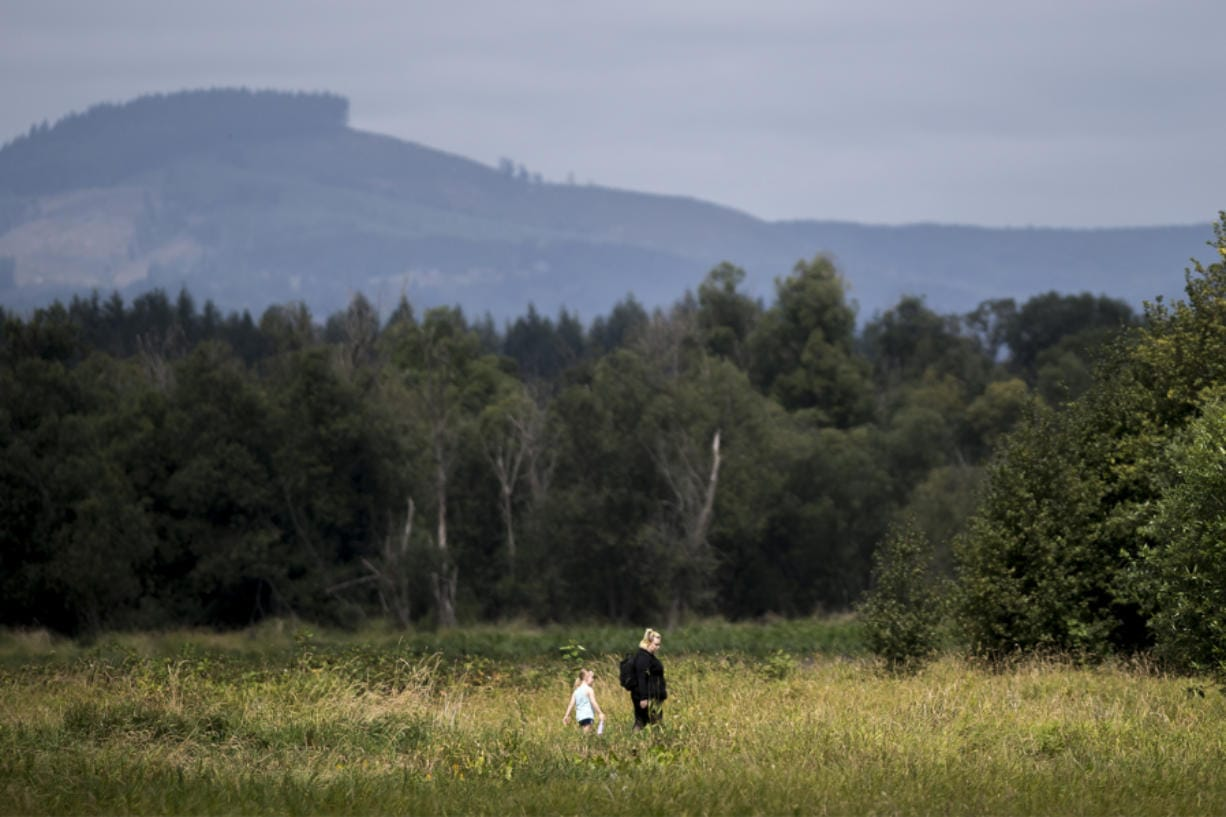 Maxine Deschand, 6, left, and her mother, Brianna Deschand, walk through the Ridgefield National Wildlife Refuge on Thursday. The refuge has proved a crucial habitat for the region's endangered and threatened species, helping populations such as the Columbian white-tailed deer rebound.