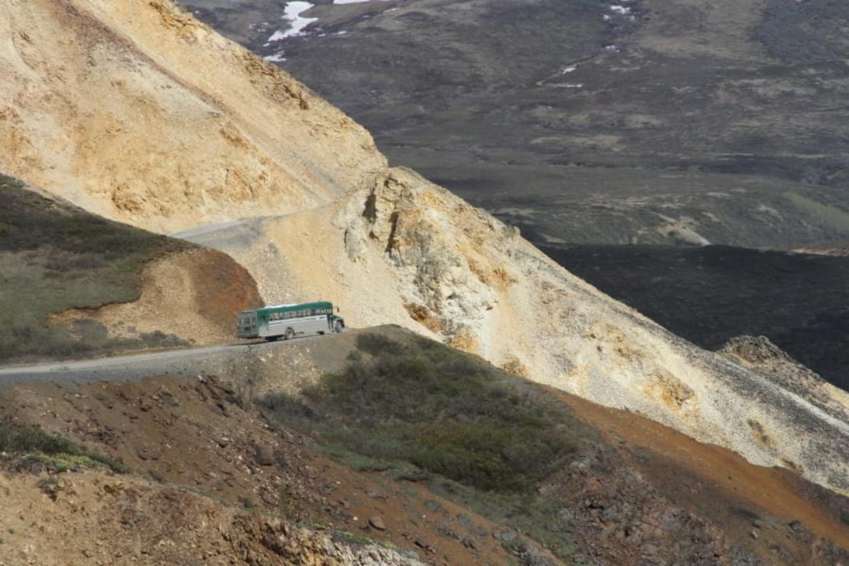 This May 27, 2016, photo shows a tourist bus near Polychome Pass on the only road inside Denali National Park and Preserve, Alaska. Park officials on Friday, Aug. 16, 2019, closed the park road at Mile 30 of the 92-mile road after a culvert washout and several mudslides in the area surrounding Polychome Pass and Eielson Visitor Center created unsafe conditions. Park officials say 300 tourists were inside the park, on the other side of the road closure (AP Photo/Mark Thiessen)