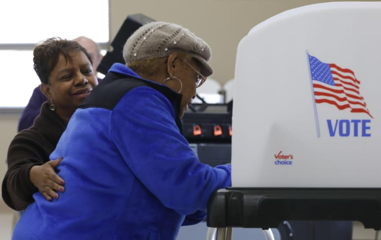 Poll Officer Linda Thompson, left, aids a voter as she takes advantage of early voting in the local primary election in Chattanooga, Tenn., in February 2016. To improve security, Tennessee election officials are trying to win approval for voting machines that produce a paper record.