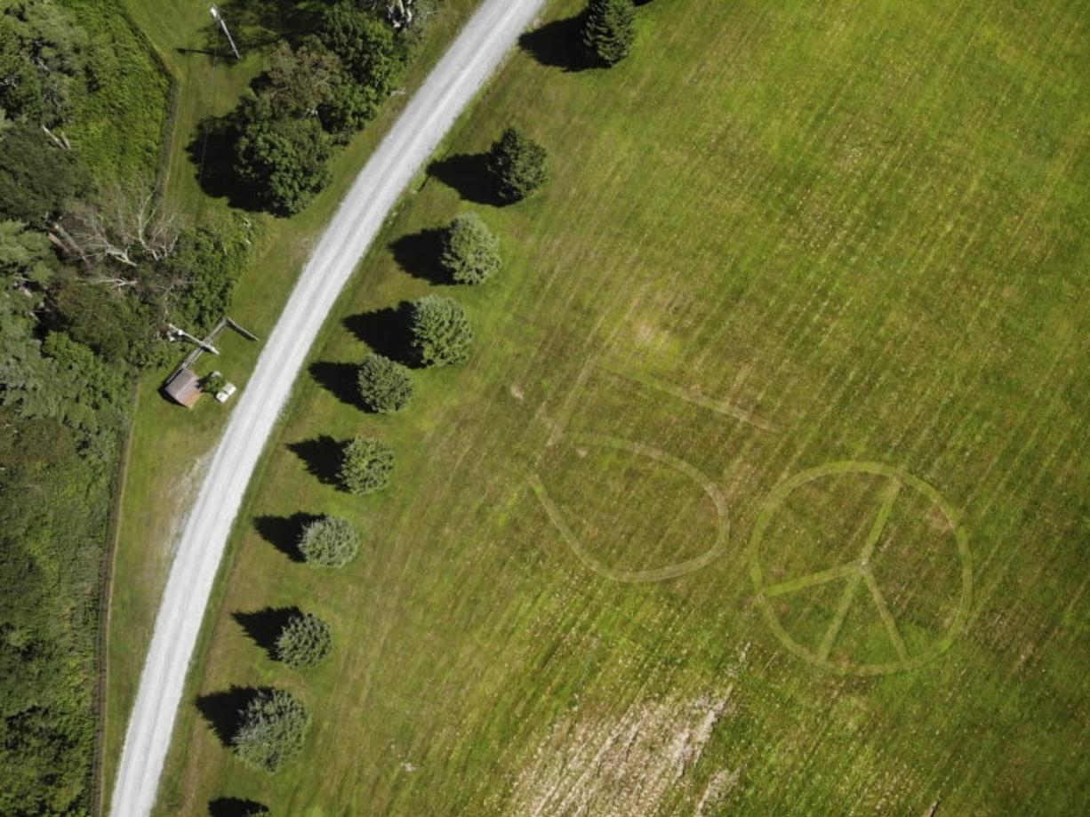 This Wednesday, July 24, 2019, photo shows the number 50 and a peace sign mowed into the grass at the site of the 1969 Woodstock Music and Arts Fair in Bethel, N.Y. Fifty years later, memories of the rainy weekend Aug. 15-18, 1969, remain sharp among people who were in the crowd and on the stage. (AP Photo/Seth Wenig)