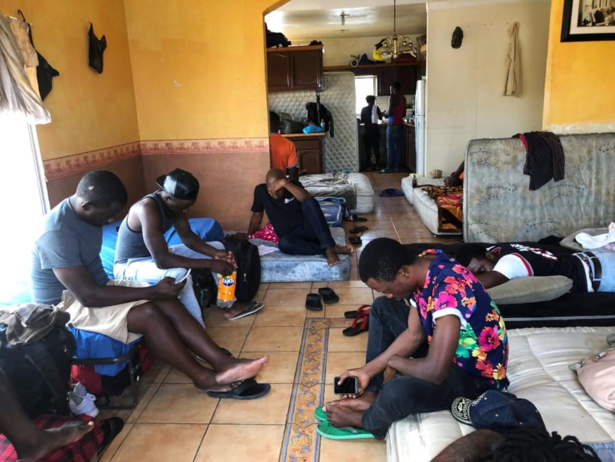 In this July 28, 2019, photo, Cameroonians wait in a rented apartment in Tijuana, Mexico, until their names are called to claim asylum in the U.S. The Cameroonian men who share 10 mattresses on the floor of a third-floor apartment above a barber shop walk every morning to the busiest U.S. border crossing with Mexico, hoping against all odds that it will be their lucky day to claim asylum. Their unlikely bet is that a sympathetic Mexican official will somehow find a spot for them.