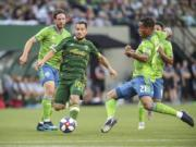 Portland Timbers' Sebastian Blanco works between Seattle Sounders, including Jordy Delem (21), during the first half of an MLS soccer match Friday, Aug. 23, 2019, in Portland, Ore.