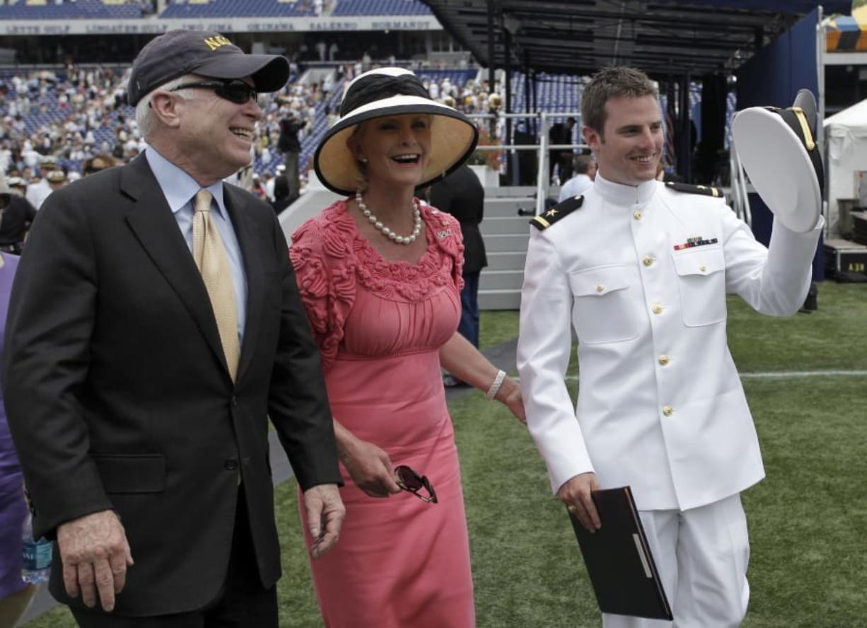 """FILE - In this Friday, May 22, 2009, file photo, Sen. John McCain, R-Ariz., left, and his wife, Cindy, walk with their son Jack after he graduated from the U.S. Naval Academy in Annapolis, Md. The family of the late Sen. John McCain says they want to build a library on land donated by Arizona State University to house his archives and provide a """"gathering place"""" for respectful dialogue. (AP Photo/Rob Carr, File)"""