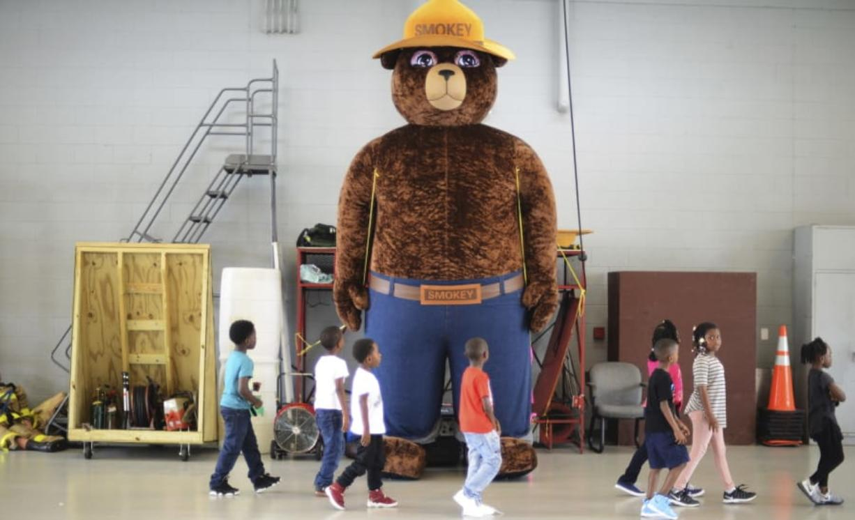 A giant Smokey Bear figure greets children at a fire department open house in Kinston, N.C., in 2017. The icon of the longest-running public service campaign in the U.S. was born on Aug. 9, 1944. janet s.