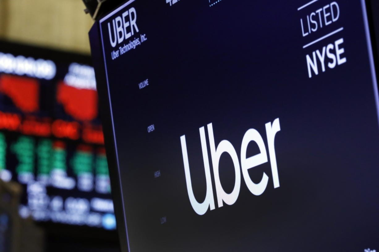 FILE - In this Aug. 9, 2019, file photo, the logo for Uber appears above a trading post on the floor of the New York Stock Exchange. Texas Gov. Greg Abbott has announced that Uber will receive a $24 million state incentive package and open a new administrative hub in Dallas, bringing with it about 3,000 jobs. Abbott said in a statement Tuesday, Aug. 20, 2019, that the Dallas offices will house various corporate functions.