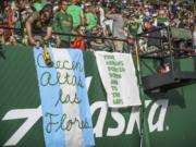 Portland Timbers fans display signs at an MLS soccer match against the Seattle Sounders in Portland on Aug. 23, 2019.. MLS is lifting its ban on signs and banners featuring an anti-Nazi symbol for the remainder of the season and the playoffs. A handful of fans in Portland were prohibited from attending matches this season after challenging a ban on the Iron Front.