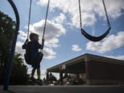 Green Mountain School kindergartners Lana Schmeusser, left, and Cara Morgan, right, play on merry-go-round in 2018. The one-school district saw a 12. 4 percent enrollment increase over 5 years.