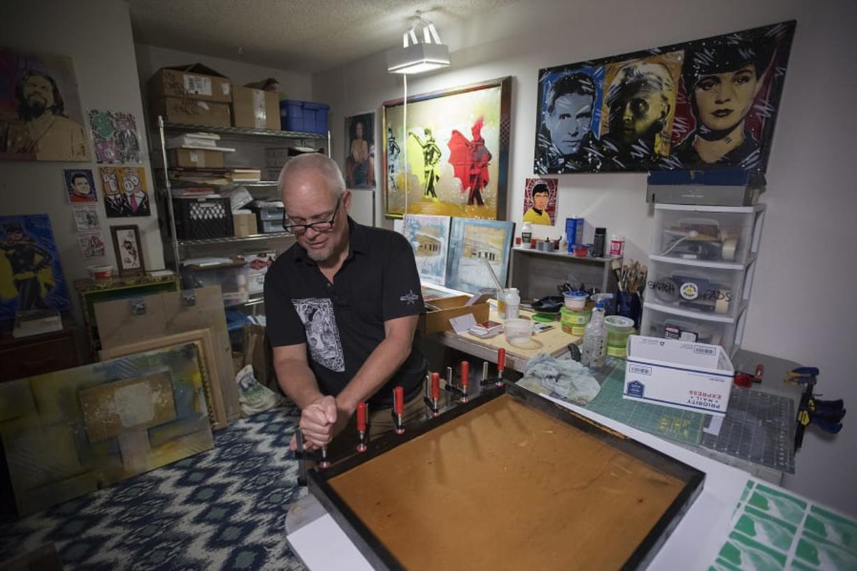 Chris Stevens, whose specialty is recycling pop culture and science fiction imagery with additional layers of strangeness and sparkle, builds a picture frame in his Salmon Creek studio. Amanda Cowan/The Columbian
