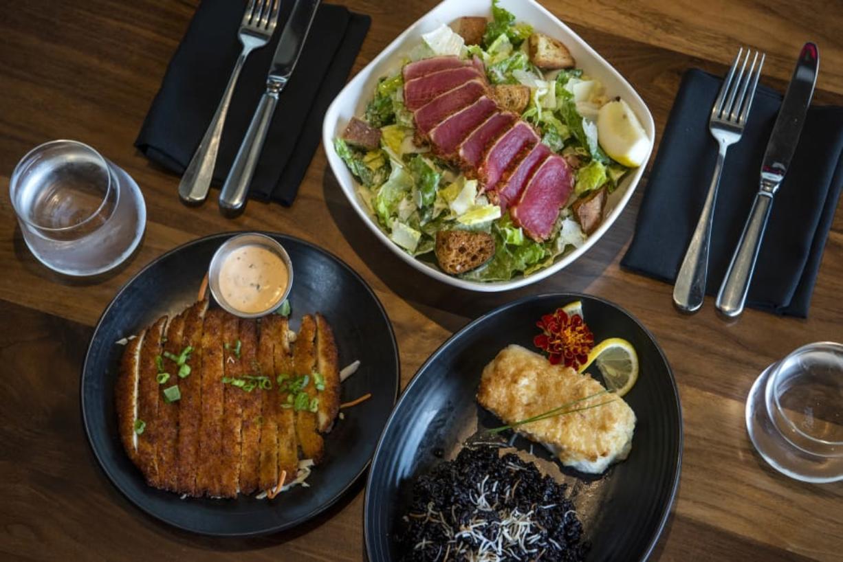 Crispy calamari, bottom left, Ahi Caesar Salad, top center, and Mac Nut Halibut, bottom right, at Tommy O's at The Camas Hotel.