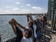 Attendees hold their hands up and recite the Serenity Prayer during the Hands Across the Bridge event on the I-5 bridge on Monday, September 2, 2019. This day marked the 19th anniversary of the event, in which people in recovery come together to share their stories and celebrate sobriety. More than 900 people walked from Esther Short Park out onto the bridge to meet the crowd walking from the Oregon side of the Columbia River.